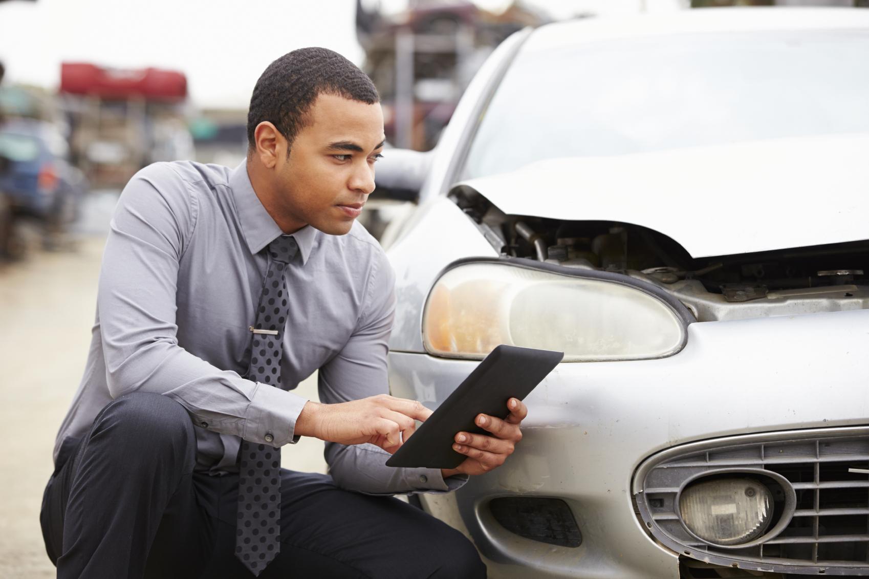 Loss Adjuster Using Digital Tablet In Car Wreck Inspection